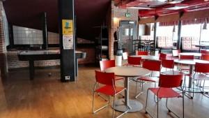 Kuvassa on Kokemäen nuorten nettikahvila sisältäpäin. Kuvassa näkyy tuoleja, pöytiä ja ilmajääkiekkopöytä.