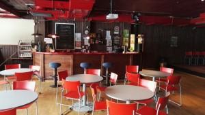 Kuvassa on Kokemäen nuorten nettikahvila sisältäpäin. Kuvassa näkyy tuoleja, pöytiä ja kahvilan tiski.