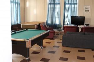 Kuvassa on Pomarkun nuorisotila sisältä. Tilassa on kaksi biljardipöytää, sohva, nojatuoleja ja televisio.