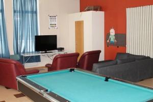Kuvassa on Pomarkun nuorisotila sisältä. Tilassa on biljardipöytä, sohva, nojatuoleja ja televisio.