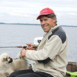 Kuvassa on Reijo Peltomaan kasvokuva. Reijon vieressä on koira.