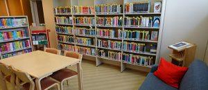 Nakkilan kirjaston kirjahylly, tuolit ja pöytä.