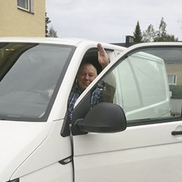 Kuvassa on Teuvo Munkki vilkuttamassa autosta.