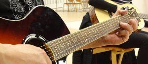Kuvassa näkyy kaksi akustisen kitaran soittajaa.