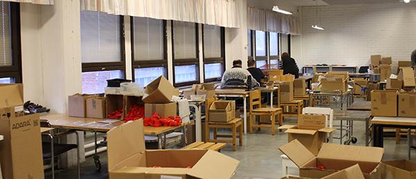 Kuvassa on muutamia ihmisiä istumassa pöydän äärellä. Ympärillä on paljon pöytiä, tuoleja ja pahvilaatikoita.