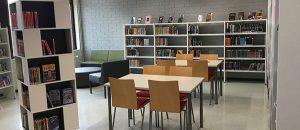 Kuvassa on Kokemäen kirjaston kirjahyllyjä, pöytiä ja tuoleja.