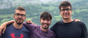 Kuvassa on kolme nuorta miestä vierekkäin ja he hymyilevät.