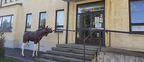 Kuvassa on Huittisten Perheneuvolan ulko-ovi, jonka edessä on portaat. Portaiden vieressä on iso kokoinen hirvipatsas.