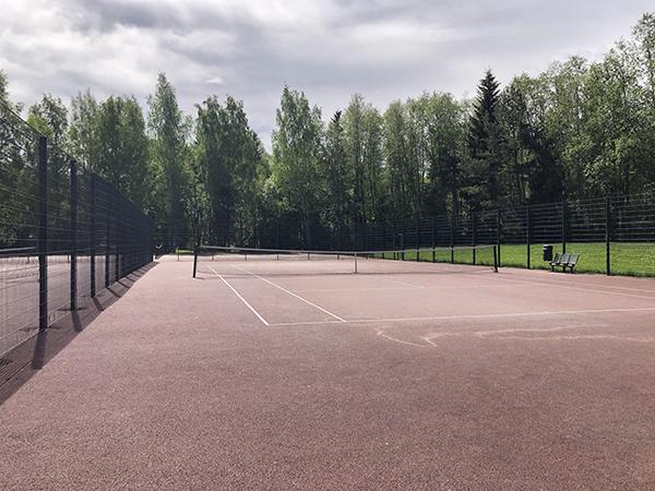 Kuvassa on tenniskenttä, joka on aidattu.
