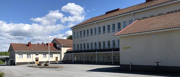 Kuvassa on vaalean ruskea kolmikerroksinen rakennus.