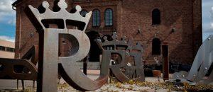 Kuvassa on Rosenlew Museon rakennus ulkoapäin. Pihassa näkyy raudasta tehtyjä isoja R-kirjaimia.