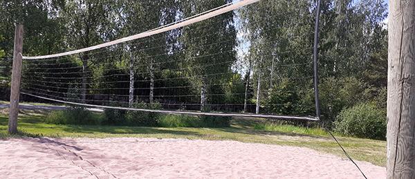Kuvassa on rantalentopallokenttä, jossa on verkko ja hiekkakenttä.