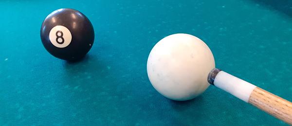 Kuvassa on biljardikeppi sekä valkoinen ja musta biljardipallo.