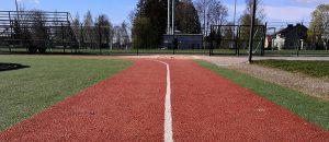 Kuvassa on urheilukentän juoksurata ja takana näkyy aita.