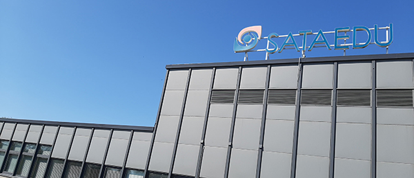 Kuvassa on Sataedun Huittisten toimipisteen rakennus. Rakennuksen katolla on Sataedun logo.
