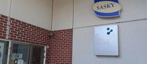 Huittisten ammatti ja yrittäjäopiston ja SAMKin Huittisten toimipisteen yhteinen pääovi ulkoapäin. Rakennuksen seinällä näkyy SAKSYn ja SAMKin kyltit.