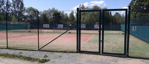 Huittisten tenniskenttä. Kentän ympärillä rautaaita ja portin ovi kiinni.
