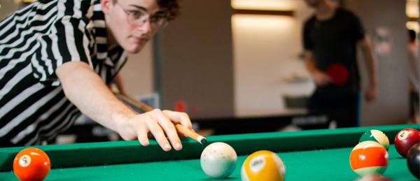 Kuvassa nuori on lyömässä biljardikepillä palloa biljaripöydällä.