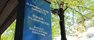 """Kuvassa on kansalaisopiston kyltti, jossa lukee """"Kansalaisopisto"""", """"Kesäyliopisto"""" ja """"Adult Education center"""""""