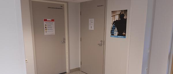 Kuvassa on käytävän nurkka, jossa on kaksi harmaata ovea.