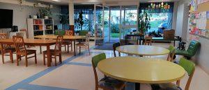 Kuvassa on pöytiä, tuoleja ja ulko-ovi.