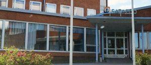 Kuvassa on punatiilinen rakennus ulkoa. Katolla on Sataedun logo.