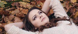 Kuvassa on henkilö, joka makaa syksyn lehtien päällä.