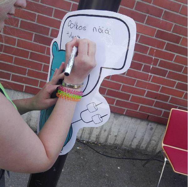 Kuvassa on nuori, joka kirjoittaa Nuokkakarhun puhekuplaan tekstiä.