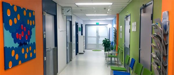 Kuvassa käytävä, jonka seinät ovat väriltää oransseja ja vihreitä. Käytävällä on tuoleja.
