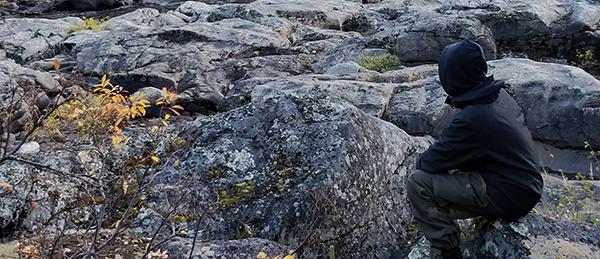 Kuvassa on henkilö, joka istuu kivikolla.