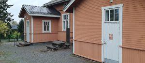 Kuvassa on oranssin värinen puutalo, jossa on kaksi valkoista ovea.