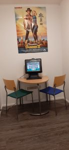 Kuvassa on kaksi tuolia, pöytä ja pelikone.