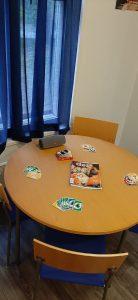 Kuvassa on pöytä ja tuoleja. Pöydällä on pelikortteja, lehtiä ja kaiutin.