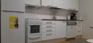 Kuvassa on keittiön kaapisto, jääkaappi, uuni ja tiskikone.
