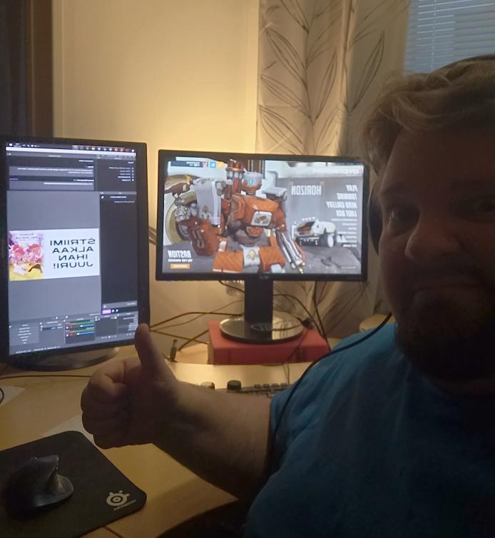 Kuvassa on henkilö, jonka takana on kaksi tietokoneen näyttöä. Näytöllä näkyy pelilähetys.