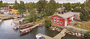 Kuvassa on satamaa, veneitä ja punainen talo.