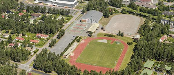 Kuva on otettu ylhäältä päin. Kuvassa näkyy maastoa, kaksi kurheilukenttää, rakennus, parkkipaikka ja puita.
