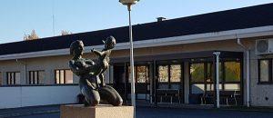 Kuvassa on terveyskeskuksen rakennus. Pihassa on patsas, jossa nainen pitää vauvaa sylissään.