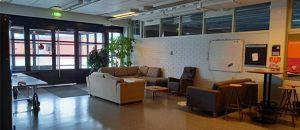 Kuvassa on eteinen, jossa on sohvia, tuoleja ja pöytiä.