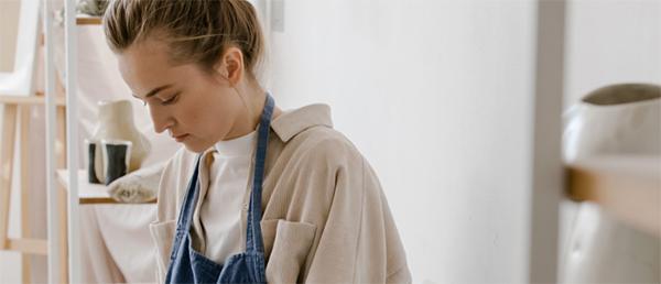 Kuvassa nainen työskentelee essu päällä.