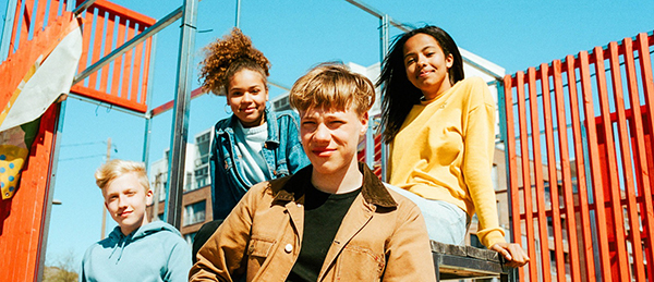 Kuvassa on neljä nuorta hymyilemässä.
