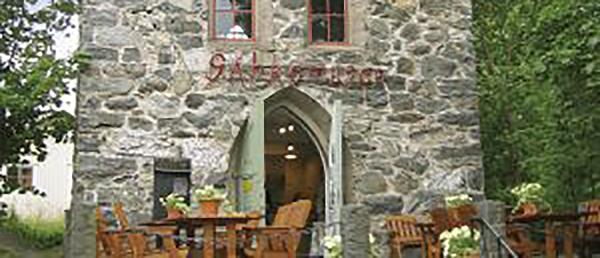 Kuvassa on kivinen rakennus, jonka edessä on kahvilapöytiä ja -tuoleja.