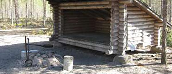Kuvassa on laavu, jonka edessä on nuotiopaikka.