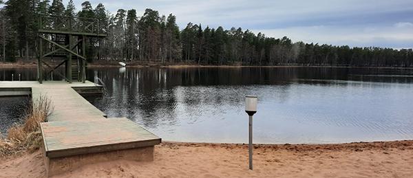 Kuvassa on hiekkaranta, laituri, vesi ja hyppytorni.