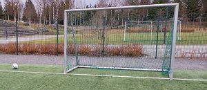 Kuvassa on jalkapallokenttä, maali ja jalkapallo.
