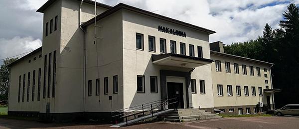 Kuvassa on valkoinen rakennus, jonka pääovella on portaat ja ramppi.
