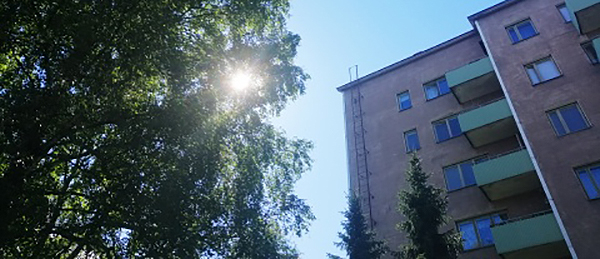 Kuvassa on puita ja korkea kerrostalo.