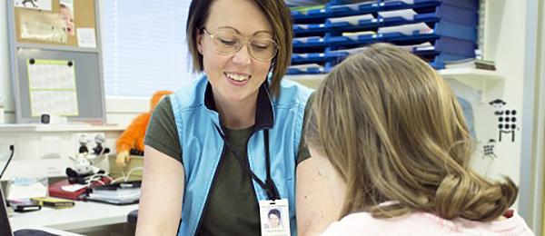 Kuvassa on terveydenhoitaja, joka keskustelee nuoren kanssa.