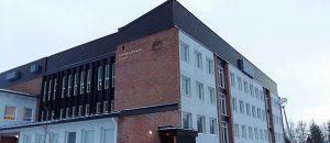 Kuvassa on punatiilinen ja monikerroksinen rakennus.