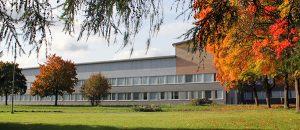 Kuvassa on matala ja leveä rakennus, jonka pihassa on puita.